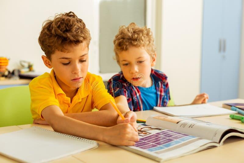 Meninos novos agradáveis que sentam-se em uma mesa imagem de stock royalty free