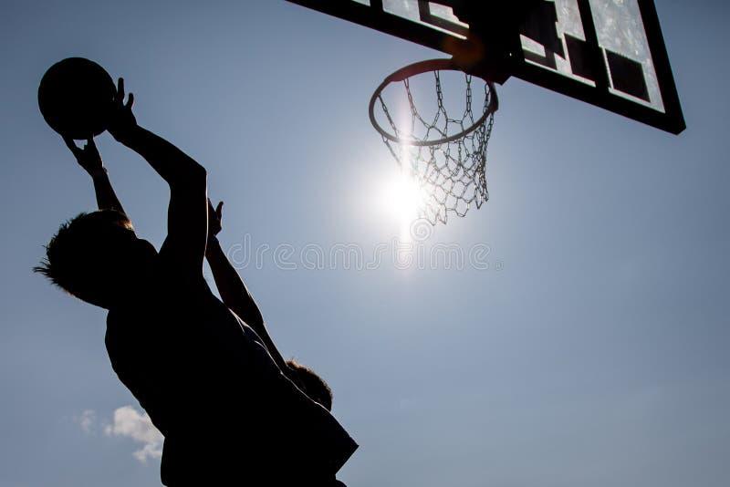 Meninos novos do basquetebol do jogo da silhueta imagens de stock