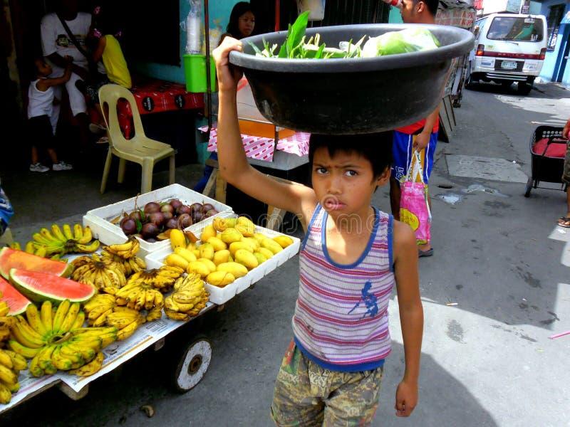 Meninos novos em um mercado do cainta, rizal, Filipinas que vendem frutas e legumes imagem de stock royalty free