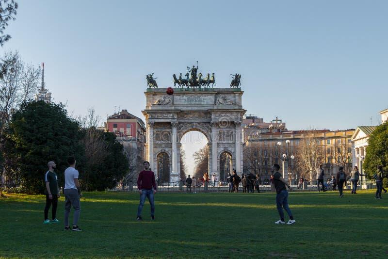 Meninos novos que jogam o futebol na frente do arco do arco triunfal da paz em Milão imagens de stock