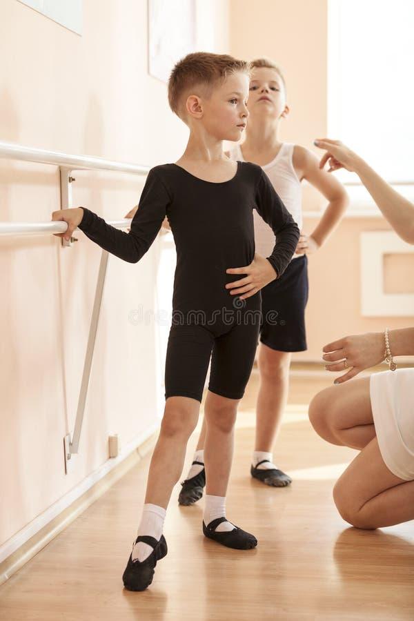 Meninos novos que trabalham na barra em uma classe de dança do bailado fotos de stock royalty free