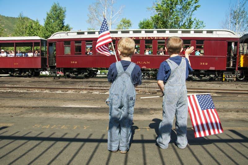 Meninos que acenam o coordenador do trem das bandeiras americanas imagem de stock