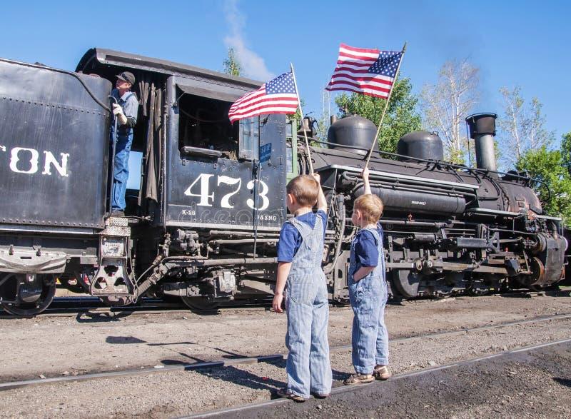 Meninos que acenam o coordenador do trem das bandeiras americanas imagens de stock