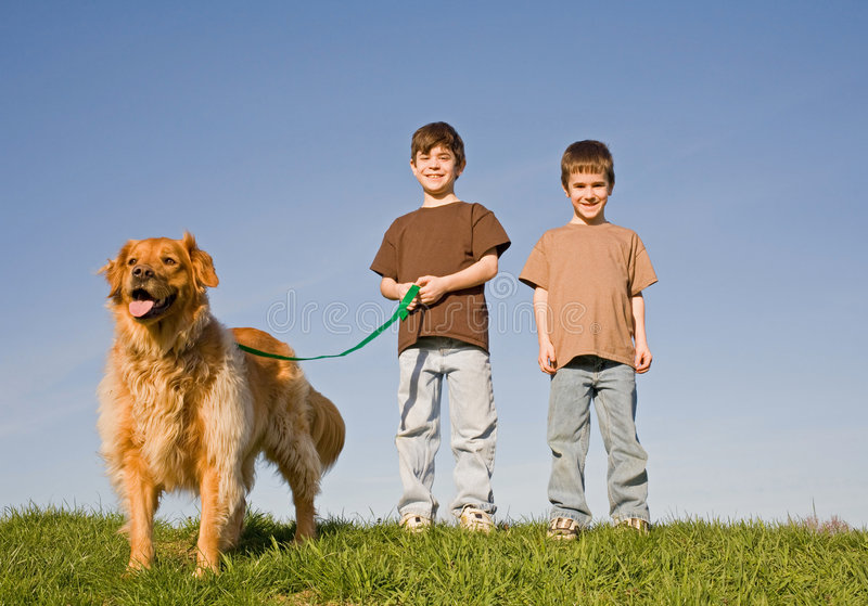 Meninos que andam o cão fotografia de stock