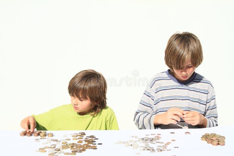Meninos que contam o dinheiro imagens de stock royalty free