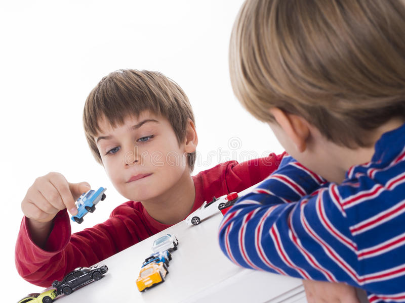 Meninos que jogam com modelos dos carros foto de stock
