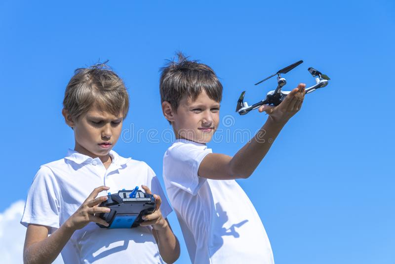 Meninos que jogam com o zangão no dia de verão fora contra o céu azul fotos de stock