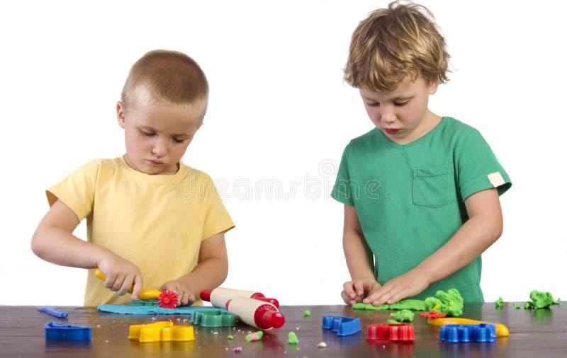 Meninos que jogam com playdough fotografia de stock