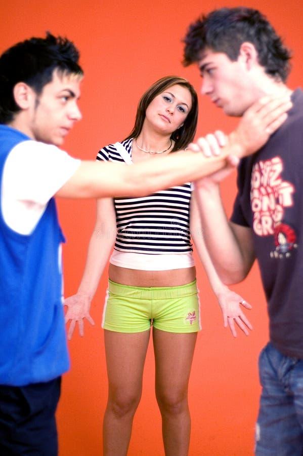 Meninos que lutam sobre a menina fotos de stock