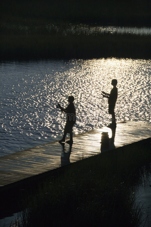 Meninos que pescam na doca. fotografia de stock