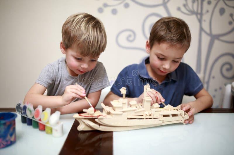Meninos que pintam o modelo de um navio de guerra imagem de stock royalty free