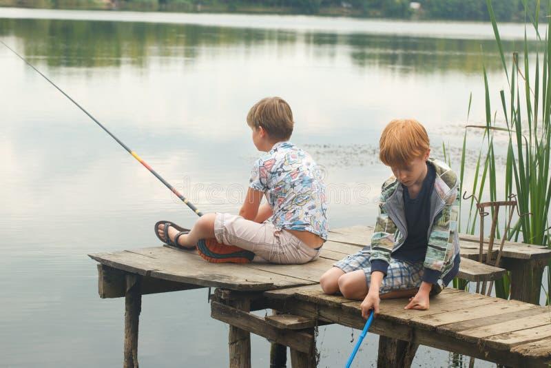 Meninos que sentam-se e que pescam de uma doca fotografia de stock