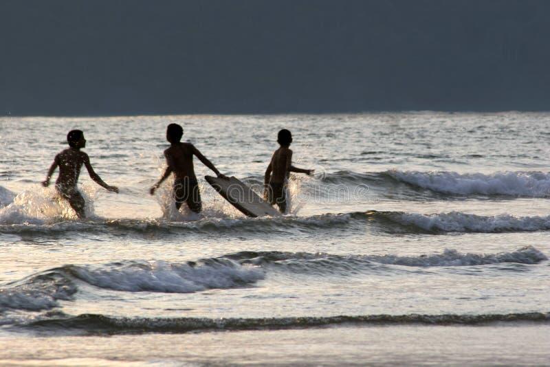 Meninos que têm o divertimento surfar no por do sol imagens de stock