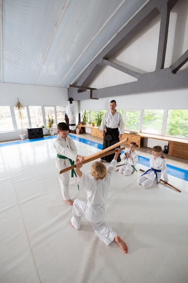 Meninos que vestem o quimono branco que tem a luta do aikido usando o jo imagens de stock royalty free