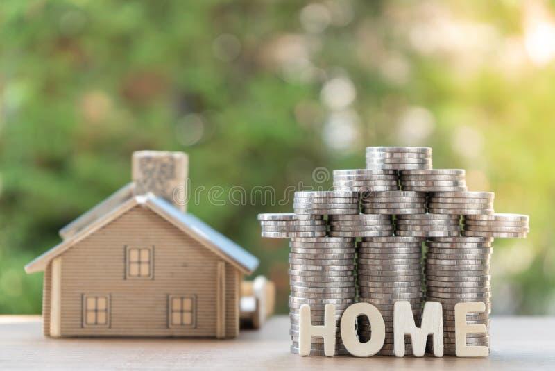 Mennicza sterta z domu modelem, domowa wiadomość, oszczędzanie plany dla mieścić, zielony tło, pieniężny pojęcie obrazy stock