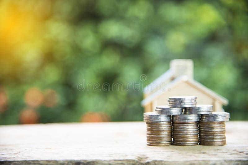 Mennicza sterta z domu modelem, savings plany dla mieścić, zielony tło, pieniężny pojęcie zdjęcie royalty free