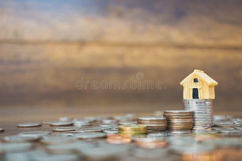 Menniczy pieniądze i dom modelujemy na drewnianym tle zdjęcie stock