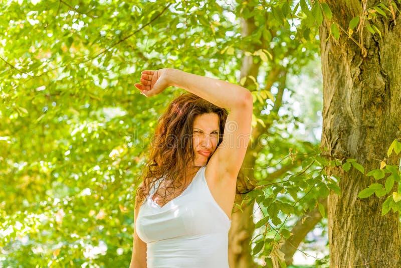 Menopauzalna kobieta obwąchuje pachy zdjęcia royalty free