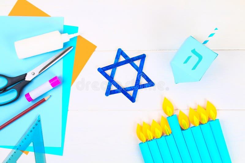 Menorah, dreidel, sevivon,大卫王之星用他们在一张白色木桌上的自己的手 孩子的DIY Chanuka的庆祝 免版税库存图片