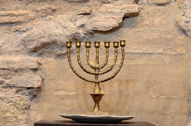 Menorah against the ancient stone wall stock photos