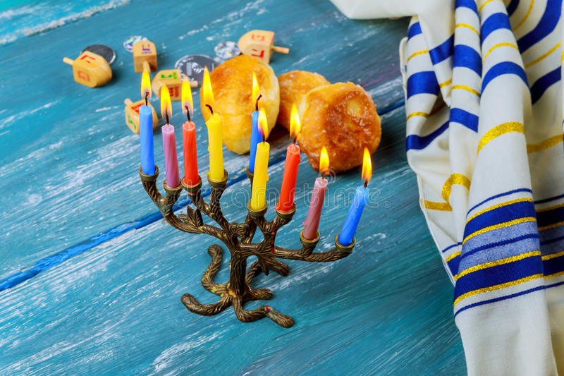 The menorah with candles and sweet donuts are traditional Jewish symbols royalty free stock photography