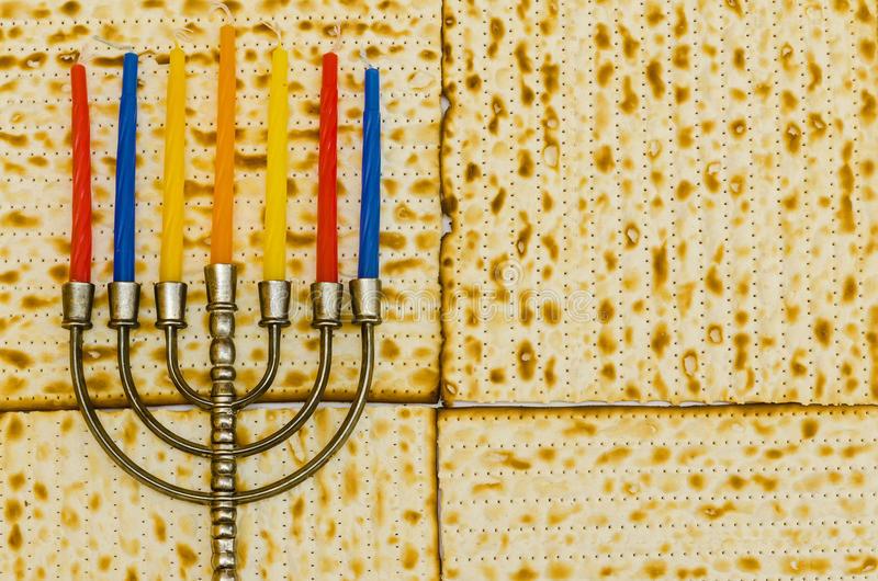 Menorah with colorful candles in front of Matzot stock images