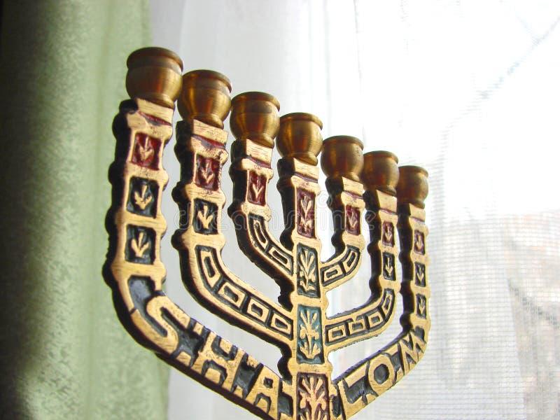 Menorah de bronce en la ventana foto de archivo libre de regalías