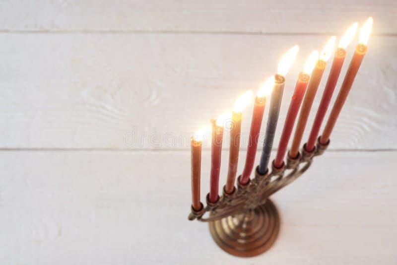 Menorah de Jánuca con las velas ardientes en la tabla de madera blanca fotos de archivo