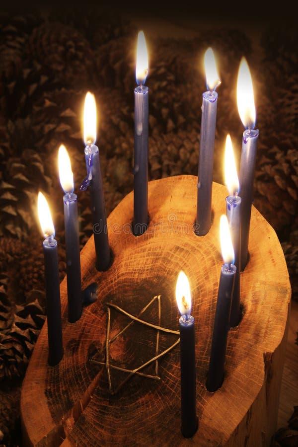 Menorah en bois ouvré de Hanoucca de rondin avec l'encart d'étoile de David, bougies allumées photographie stock libre de droits