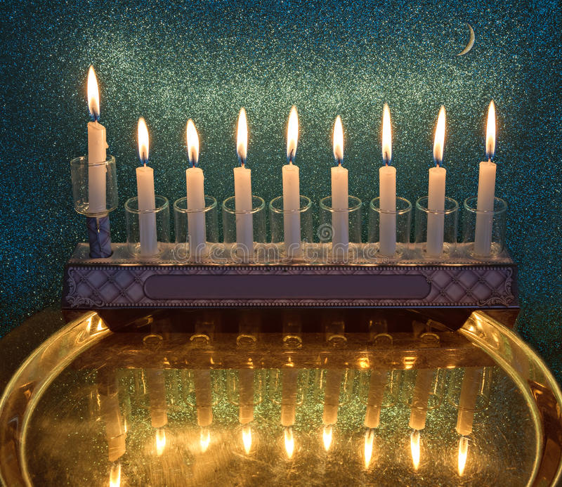 Menorah with glitter light of candles is a traditional symbol for Hanukkah holiday. Composite image with the use of of my own photos of menorah with burning stock photo