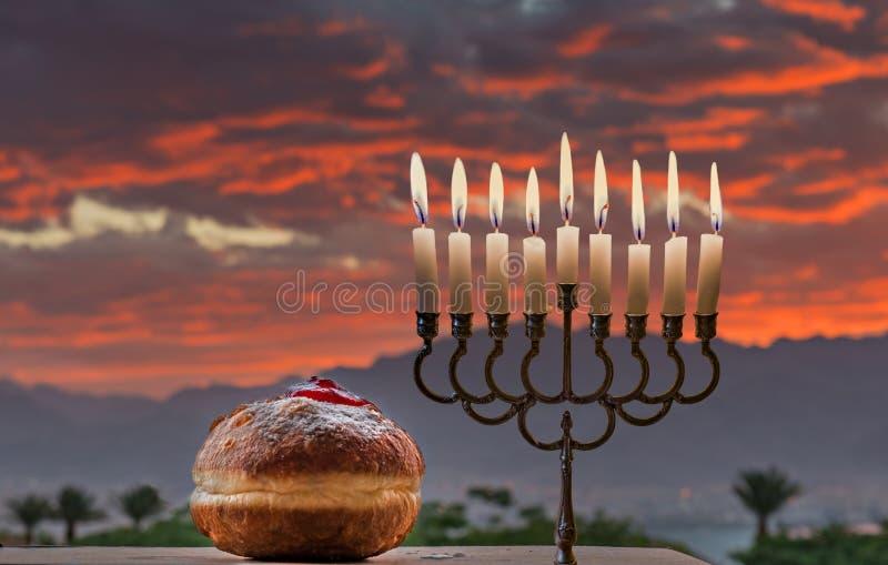 Menorah i słodcy donuts jesteśmy Hanukkah Żydowskimi wakacyjnymi symbolami zdjęcie stock