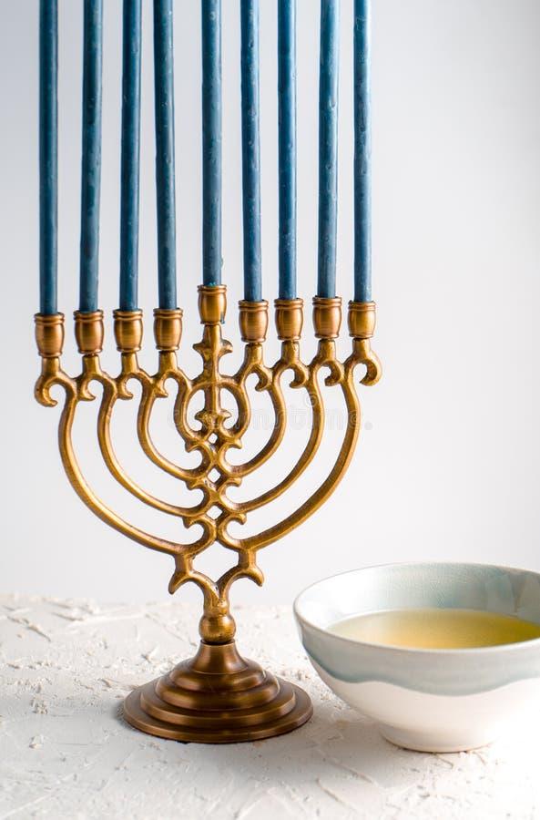 Menorah Jánuca de cobre amarillo con las velas y la mantequilla azules en un cuenco imágenes de archivo libres de regalías