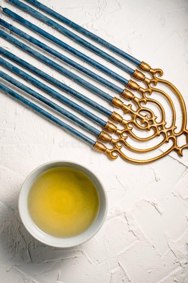 Menorah Jánuca de cobre amarillo con las velas y la mantequilla azules en un cuenco en una tabla blanca imagen de archivo libre de regalías