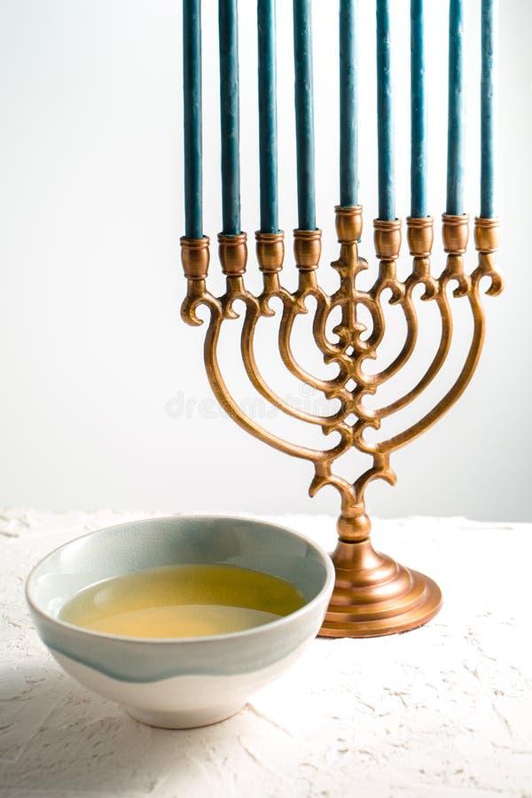 Menorah Jánuca de cobre amarillo con las velas y la mantequilla azules en vista lateral del cuenco foto de archivo