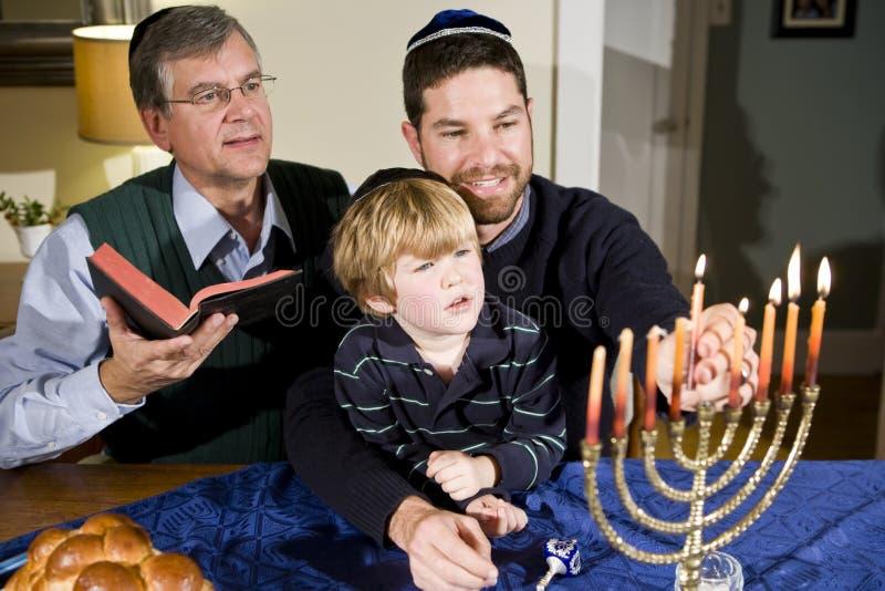 Menorah juif de Hanukkah d'éclairage de famille photo libre de droits