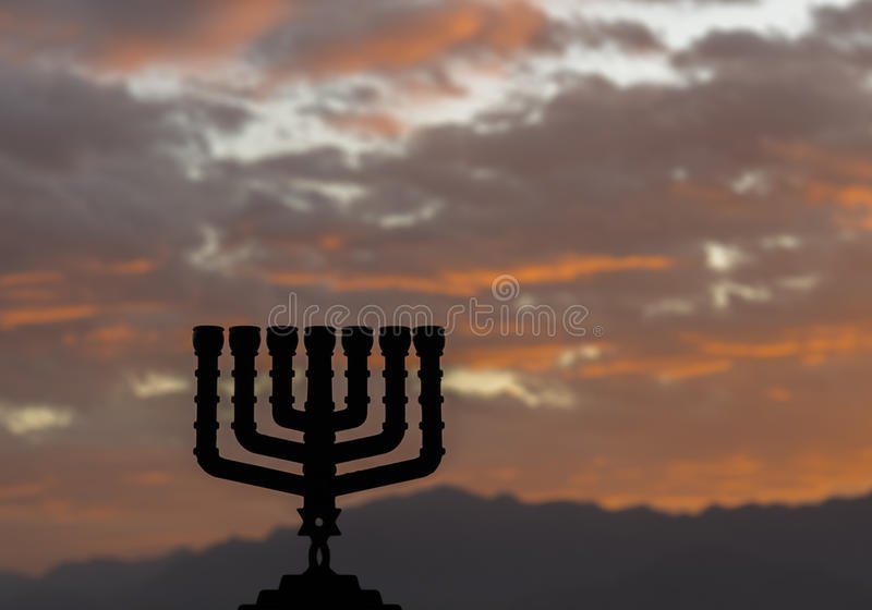 Menorah is a major traditional Jewish symbol for Hanukkah holiday. Low key image slightly toned for inspiration of retro style and feast ceremony. Selective stock photography