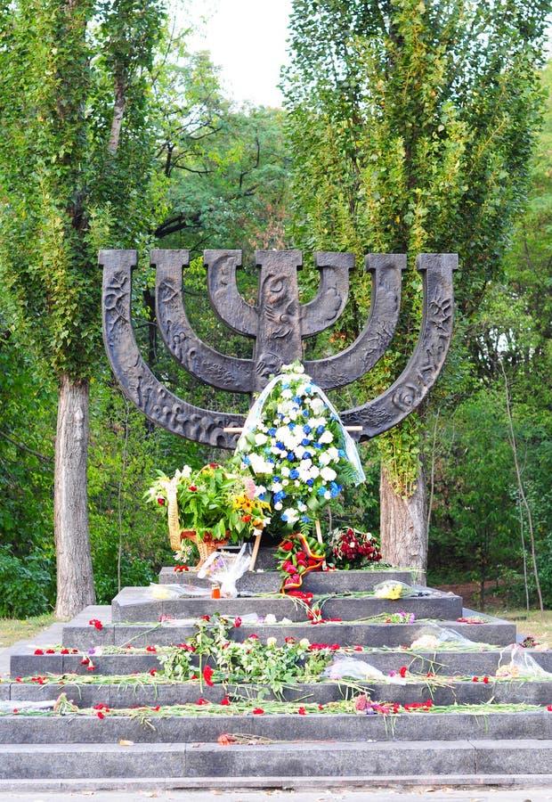 A menorah memorial with flowers dedicated to jewish people executed in 1941 in Babi Yar in Kiev. Holocaust. KIEV - UKRAINE, SEPTEMBER - 23, 2015: A menorah royalty free stock image