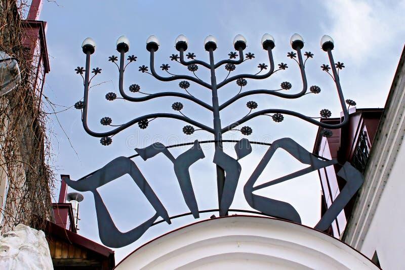 Menorah sopra l'entrata ad una vecchia sinagoga ebrea nel quadrato di Szeroka nel distretto di Kazimierz della città, Cracovia immagini stock libere da diritti