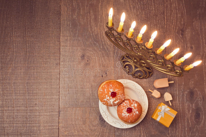 Menorah and sufganiyot on wooden table for Hanukkah celebration. View from above stock photography