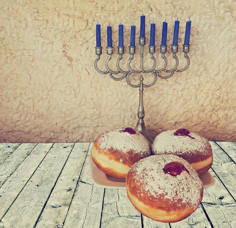 Menorah and sweet donuts are Hanukkah Jewish holiday symbols royalty free stock images