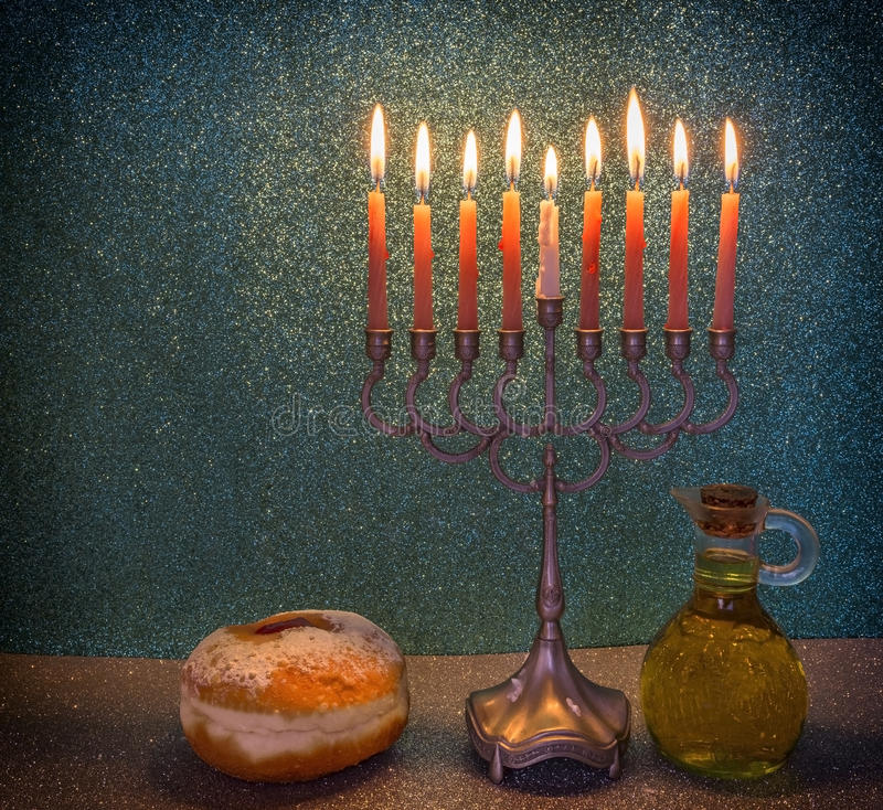 Menorah is traditional Jewish symbol for Hanukkah holiday. Jewish menorah with candles, sweet donuts and jar of olive oil are traditional symbols for feast stock image