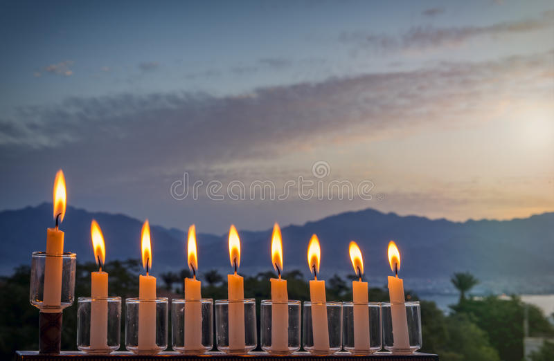 Menorah is traditional Jewish symbol for Hanukkah holiday. Photo was taken at sunrise using burning decorative candles as foreground for inspiration of Jewish stock photography