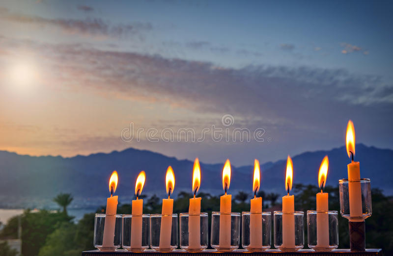 Menorah is traditional Jewish symbol for Hanukkah holiday. Photo was taken at sunrise using the nine burning decorative candles as foreground for inspiration of royalty free stock images