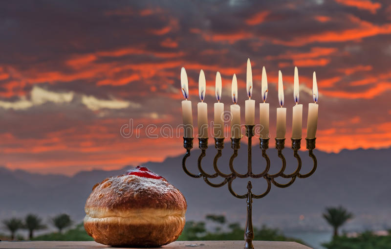 Menorah y los anillos de espuma dulces son símbolos judíos del día de fiesta de Jánuca foto de archivo