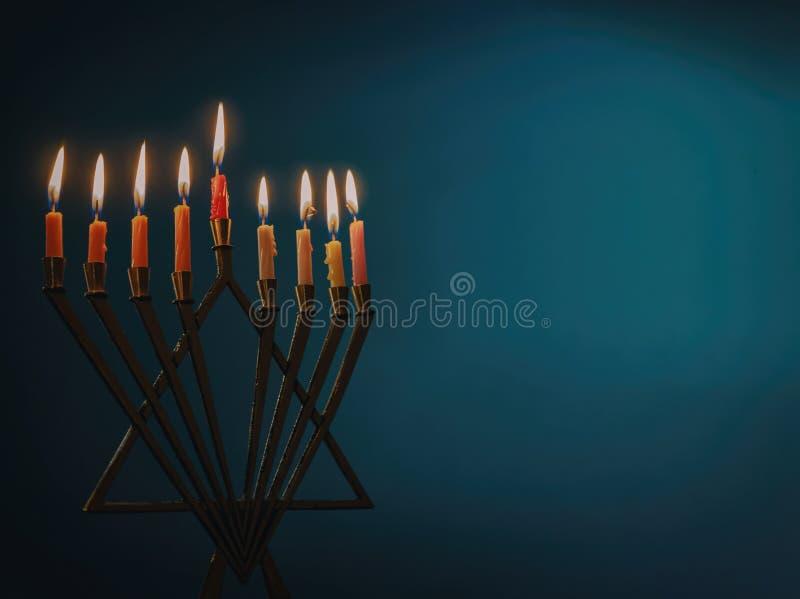Menorah z kolorowymi świeczkami dla Hanukkah na bławym tle, zakończenie w górę obraz royalty free