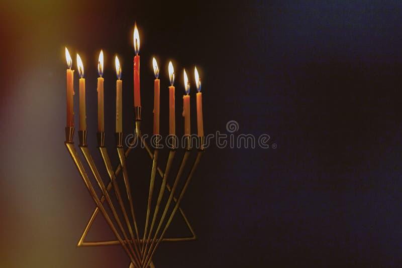 Menorah z kolorowymi świeczkami dla Hanukkah na bławym tle, zakończenie w górę fotografia stock