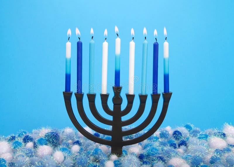 Menorah z płonącymi świeczkami na błękitnym tle zdjęcie royalty free