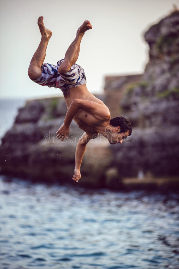 Menorca, España - 8 de septiembre: Hombre joven que salta del acantilado en el mar, en el 8 de septiembre de 2014 en Menorca, Esp fotos de archivo libres de regalías