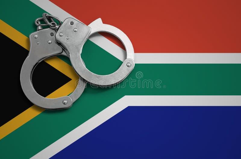Menottes de drapeau et de police de l'Afrique du Sud Le concept du crime et des offenses dans le pays photos stock