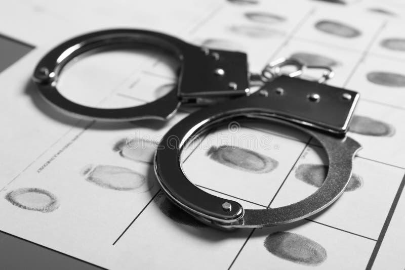Menottes de police et carte criminelle d'empreintes digitales sur la table photographie stock libre de droits